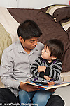 Two year old toddler boy with father read to talking interaction