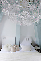 A large 'Maskros' lamp from Ikea brings a spark of playful energy to the calm colours of the bedroom