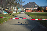"""Switzerland. Canton Ticino. Lugano. Police line. The schools are closed. Nobody can enter the courtyard  Due to the spread of the coronavirus (also called Covid-19), the Federal Council has categorised the situation in the country as """"extraordinary"""". It has issued a recommendation to all citizens to stay at home, especially the sick and the elderly. The Federal Council (German: Bundesrat, French: Conseil fédéral, Italian: Consiglio federale, Romansh: Cussegl federal) is the seven-member executive council that constitutes the federal government of the Swiss Confederation. From March 16 the government ramped up its response to the widening pandemic, ordering the closure of bars, restaurants, sports facilities and cultural spaces. Only businesses providing essential goods to the population – such as grocery stores, bakeries and pharmacies – are to remain open. 18.03.2020 © 2020 Didier Ruef"""