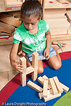 Education Preschool 3-5 year olds block area girl building with wooden blocks vertical