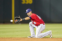 Oklahoma City RedHawks shortstop Jiovanni Mier (14) fields a ground ball during the Pacific Coast League baseball game against the Round Rock Express on August 1, 2014 at the Dell Diamond in Round Rock, Texas. The Express defeated the RedHawks 6-5. (Andrew Woolley/Four Seam Images)
