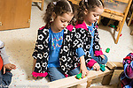 Education preschool 4-5 year olds identical twin girls playing with vehicles on roadway made from blocks, using opposite hands