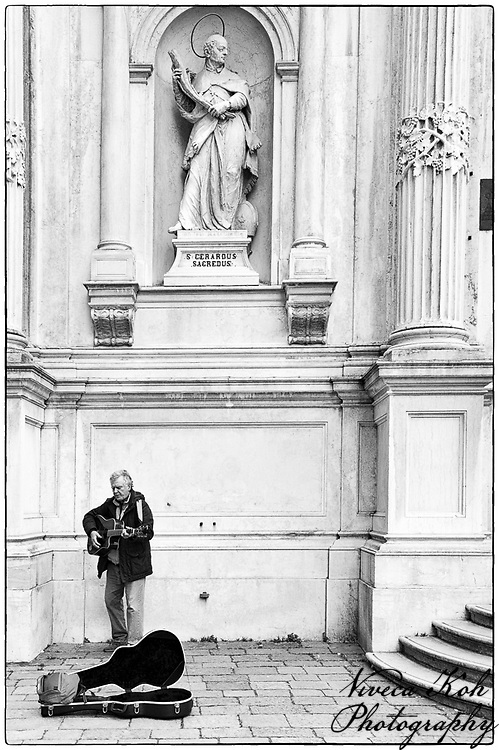 Busker playing guitar and singing outside a church in Venice, Italy.