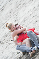 Aberystwyth Wales UK, Thursday 12 May 2016<br /> UK Weather: A young couple play fighting on the sandy beach at the seaside in Aberystwyth, on the Cardigan Bay coast of west Wales, enjoying a last day of warm weather in the current mini-heatwave. <br /> The temperatures are set to fall over the coming days, with bright but colder conditions prevailing over the country