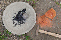 Holzkohle wird zerkleinert, um aus den Kohlekörnern schwarze Farbe herzustellen mit Wasser und Kleister, Stein wird mit dem Hammer zerkleinert, um buntes Gesteinsmehl zu erhalten, mit dem sich eine schöne Farbe anmischen lässt, Kinder malen mit selbstangemischten Erdfarben, Farbe aus verschiedenfarbiger Erde