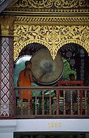 Asie/Laos/ENV Ventiane/Luang Prabang: Vat Xieng Thong - Moine tapant sur un gong