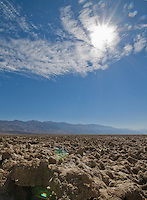 Sun and clouds over the Devil's Golf Course, an area of wind- and rain-sculpted salt and mud  in Death Valley National Park, California.