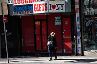 NEW YORK, NY - NOVEMBER 16: A woman passes by a souvenir store closed due to pandemic situation in Times Square on November 16, 2020 in New York. Some souvenir shops are closing and others struggling to survive the covid-19 pandemic, as no tourist visit NYC due to the virus surging again and many travel restrictions still in place, where international arrivals in main airports were down by 93 percent, according to Port Authority data. (Photo by Eduardo MunozAlvarez/VIEWpress)