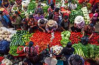 Chichicastenango, Guatemala.  Buying Fruits and Vegetables, Indoor Market, Sunday Morning.