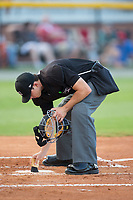 Umpire Steven Hodgins cleans off home plate during the Appalachian League game between the Danville Braves and the Burlington Royals at Burlington Athletic Stadium on August 12, 2017 in Burlington, North Carolina.  The Braves defeated the Royals 5-3.  (Brian Westerholt/Four Seam Images)