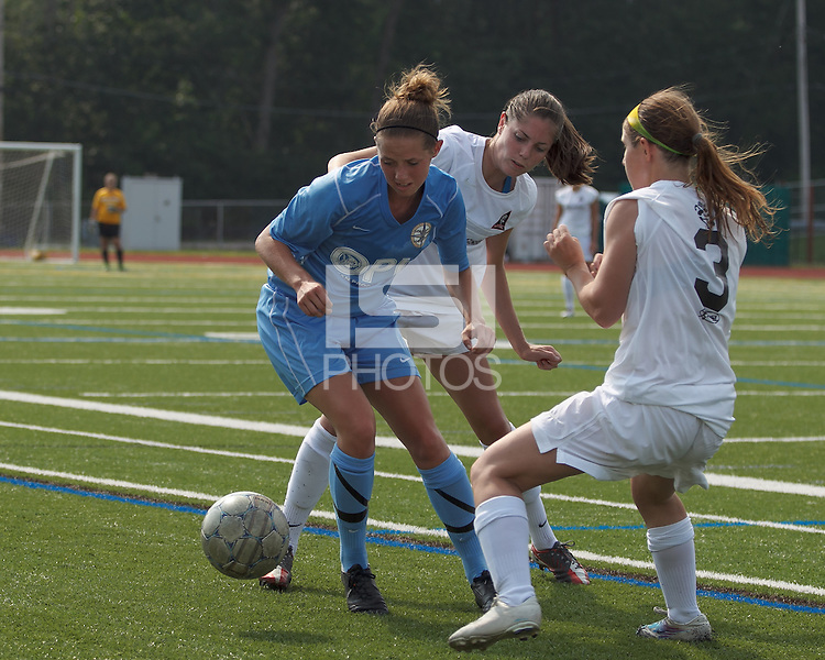 Seacoast United Mariners midfielder Taylor Littlefield (5) works to clear ball as Boston Aztec defender Jessica Morrow (26) and Boston Aztec forward Brittany Russo (3) double team. In a Women's Premier Soccer League (WPSL) match, Boston Aztec (white) defeated Seacoast United Mariners (blue), 2-1, at North Reading High School Stadium on Arthur J. Kenney Athletic Field on on June 23, 2013. Due to injuries through the season, Seacoast United Mariners could only field 10 players.