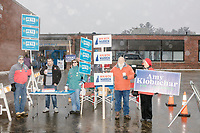 People hold campaign signs for various presidential candidates outside the polling location at James Mastricola Upper Elementary School as Merrimack Ward 1 Primary Voting begins in Merrimack, New Hampshire, on Tue., Feb. 11, 2020.