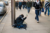 A homeless man begs from post-Christmas shoppers in High Street Kensington, London.