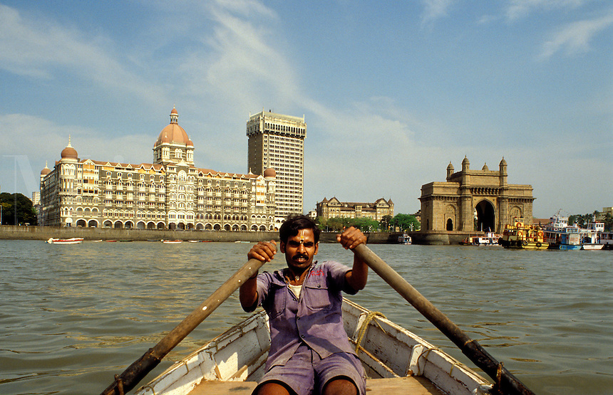 India. Mumbai/Bombay.  Waterfront with Taj Mahal and Oberoi Hotels and Gateway to India, and boatman. The Gateway was built to commemorate the visit to India of King George V and Queen Mary.  It stands on the Chatrapati Shivaji Marg. .