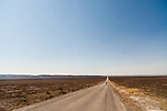 Whitehorse road in Southeast Oregon stretches off to a vanishing point as a man walks its gravel-covered surface on a hot summer afternoon after a fire burned the area.