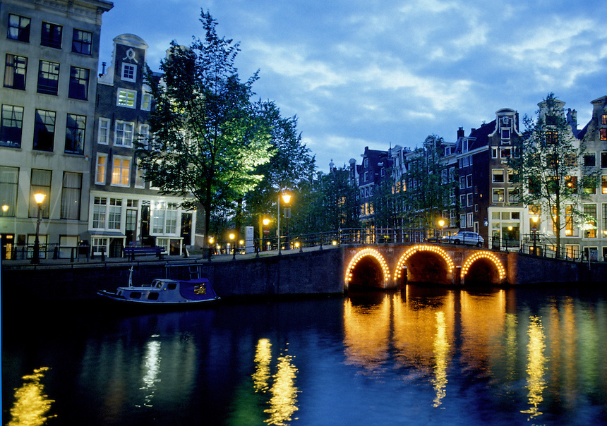 An Amsterdam city square along a canal with lights at night. Amsterdam, The Netherlands.
