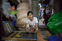 """Ma Phyu*, 14 years, baking cakes. She is employed by Nila* and her husband who run a home-based business baking cakes and packaging dry noodles which are sold in local markets. """"We work about 10 hours a day and support our families who live in a village nearby with our income. We all live together here and share a room upstairs in the house. It´s ok for us to do this work and we don`t find it too tiring."""""""