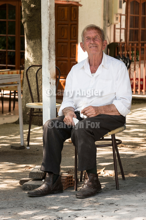 A man sits by a roadhouse, Kastraki, Greece