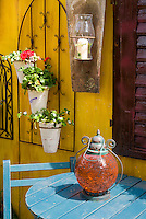Pretty scene in front of house with blue patio table and chair furniture, hanging pots, Mediterranean feel, lanterns, flea market recycled finds using old things in the garden, pot says Provence, yellow and blue and red color theme, charming wall and shutter