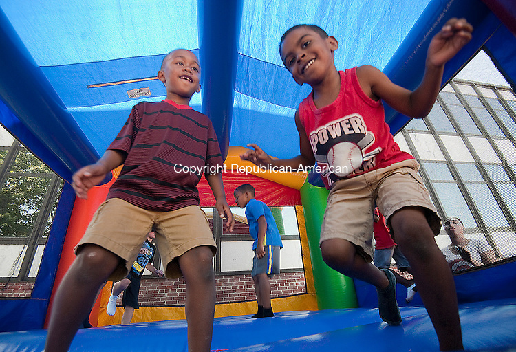 WATERBURY, CT--- -081415JS08- Liam Montgomery and Aydan Ruiz, enjoy their time in the bounce house during Camp Summer Sunshine Friday at Chase School in Waterbury. Jim Shannon Republican-American