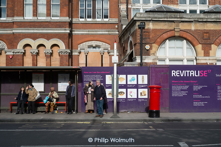 Passengers at a bus stop outside the boarded up Walworth Town Hall, which is awaiting refurbishment by Southwark Council.