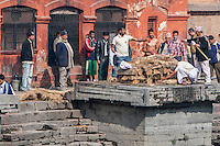 Nepal, Pashupatinath.  Cremation Stages.  Lighting the Fire Underneath the Corpse, Wrapped in a White Sheet, while Family Members Look on.  A member pours water or ghee on the corpse.