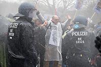 """Sogenannten """"Querdenker"""" sowie verschiedene rechte und rechtsextreme Gruppen hatten fuer den 18. November 2020 zu einer Blockade des Bundestag aufgerufen. Sie wollten damit verhindern, dass es eine Abstimmung ueber das Infektionsschutzgesetz gibt.<br /> Es sollen sich ca. 7.000 Menschen versammelt haben. Sie wurden durch Polizeiabsperrungen daran gehindert zum Reichstagsgebaeude zu gelangen. Sie versammelten sich daraufhin u.a. vor dem Brandenburger Tor.<br /> Im Bild: Die Polizei setzt nach Aufloesung der Kundgebung und mehrfachen Flaschenwuerfen vor dem Brandenburger Tor Wasserwerfer ein. Etliche Demonstranten waren mit entsprechender Schutzkleidung (Schutzbrillen und Regenkleidung) darauf vorbereitet. Der Demonstrant mit Brille haelt ein Megafon in der linken Hand und hat ein Plakat mit Mahatma Ghandi vor dem Bauch. <br /> 18.11.2020, Berlin<br /> Copyright: Christian-Ditsch.de"""