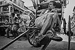 A ricksaw puller weariing an Adidas shoe takes rest on his rickshaw in Kolkata, India.