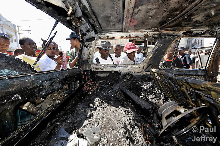 Haitians examine the inside of a car after it was burned in a political protest outside a Catholic mass in Port-au-Prince that marked the one-year anniversary of the January 12, 2010, earthquake that devastated Haiti. The car, which belonged to Father Allan Francois, was set afire by protestors upset about the government's management of the quake recovery. Held in the shadows of the ruins of the city's Catholic cathedral, the Mass was one of many special observances held throughout the Caribbean nation...