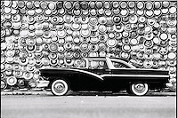 Classic car, Crown Victoria parked in front of a wall of hub caps.