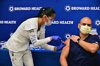 FORT LAUDERDALE, FLORIDA - DECEMBER 23: Leonida Lipshy, RN in the COVID unit at the Broward Health Medical Center, gives Miguel Pardo, RN, emergency department, a heart sticker after receiving a shot of the Moderna COVID-19 vaccine at Broward Health Imperial Point on December 23, 2020 in Fort Lauderdale, Florida. Broward Health Medical Center began vaccinating frontline healthcare workers last week with the Pfizer-BioNtech COVID-19 vaccine and are continuing to inoculate frontline caregivers with both of the vaccines after the arrival of the Moderna.  <br /> CAP/MPI10<br /> ©MPI010/Capital Pictures