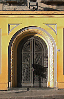 A beautiful wrought iron door to a building intricately decorated and painted in yellow and grey. Montevideo, Uruguay, South America