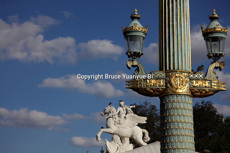 Ornate street lamp in Concorde Square Place de la Concorde with the statue of Renommée, or the fame of the king of Tuileries in the background. Paris. France