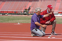 ANTHONY REYES Northwest Arkansas Times<br />Arkansas men's track coach John McDonnell talks with Bob Gago, with Mondo Corporation, about the surface and the lane painting at the John McDonnell Field in Fayetteville.
