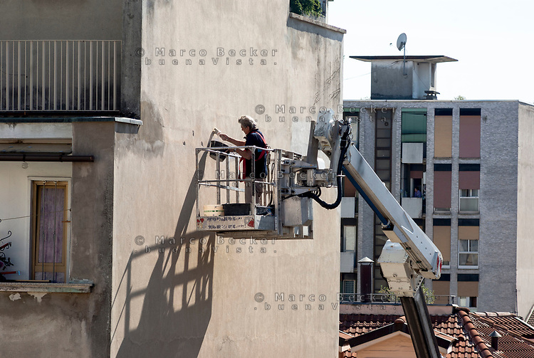 Milano, quartiere Bovisa, periferia nord. Un uomo su piattaforma aerea effettua lavori di manutenzione ad un edificio --- Milan, Bovisa district, north periphery. A man on aerial platform performing maintenance work at a building
