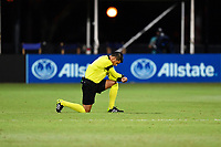 LAKE BUENA VISTA, FL - JULY 26: Referee Victor Rivas takes a knee during a game between Vancouver Whitecaps and Sporting Kansas City at ESPN Wide World of Sports on July 26, 2020 in Lake Buena Vista, Florida.