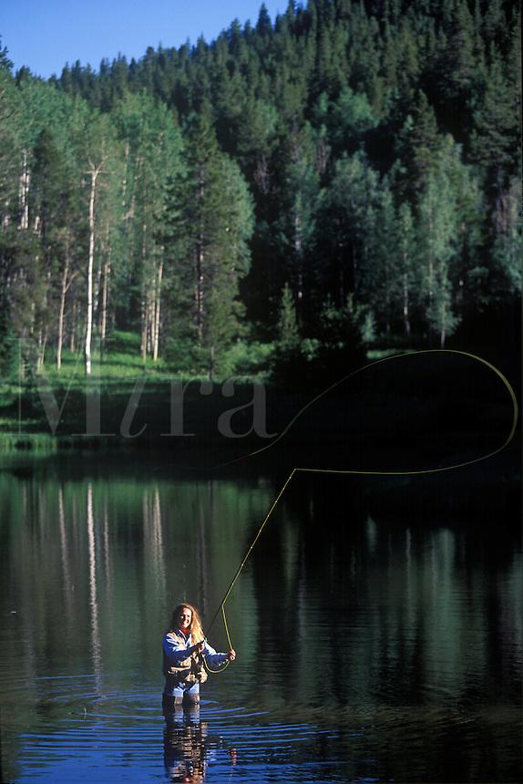 Woman fly fishing at Colorado lake near Steamboat Springs.