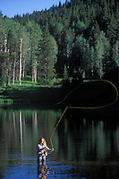 Woman fly fishing at Colorado lake near Steamboat Springs.
