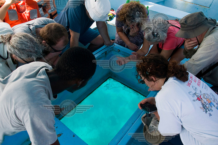 Tourists look for marine life through a glass bottomed boat in the seas of Tobago's Tyrrel's Bay.