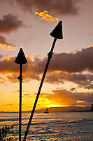 Tiki torches and a sailboat frame another spectacular sunset over the western Oahu mountains as seen from Waikiki Beach,Oahu.
