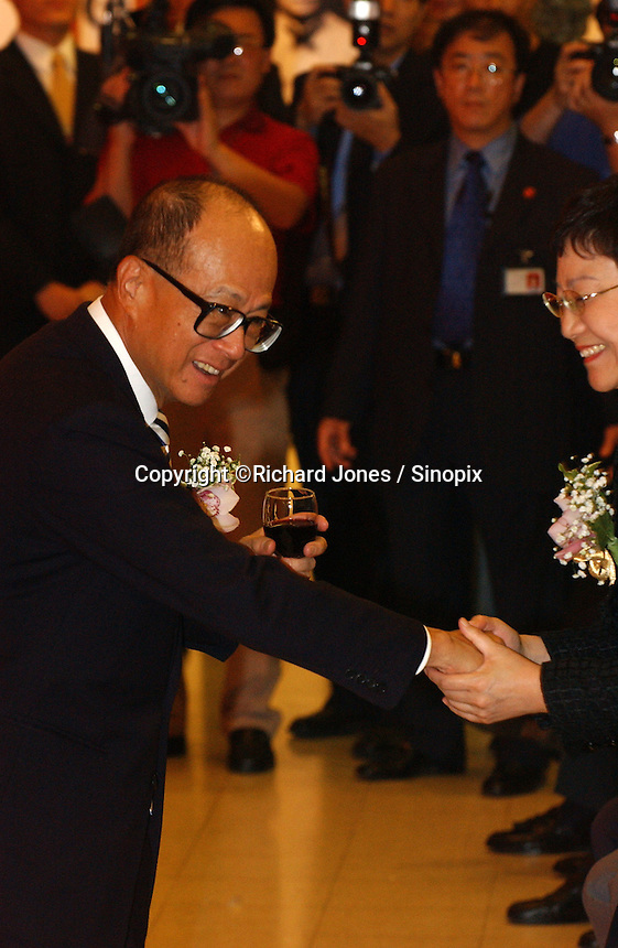 "Li Ka Shing shakes hand with Deng's youngest daughter, Deng Rong at the opening ceremony of ""Giant of the Century"" - an exhibition to commemorate the 100th Anniversary of the Birth of Deng Xiaoping in Hong Kong. The exhibition aims at introducing Deng's life to the people of Hong Kong.<br /> 26-AUG-04"