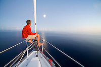 Crew of a cruising sailboat watching the moon rise in the windless Pacific High, during a Pacific crossing