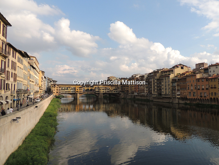 Florence, Italy - October 3, 2012:  Clouds are reflected in the Arno River in front of the Ponte Vecchio.