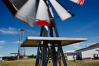 Energy generation equipment including Aermotor windmills and a Standard Oil derrick stand in a field outside the Glacier County Historical Museum in Cut Bank, Montana, USA.