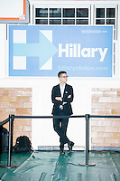 A campaign worker stands in front of a campaign sign in the press area while Democratic presidential candidate and former First Lady and Secretary of State Hillary Rodham Clinton speaks at a town hall at the McConnel Center gymnasium in Dover, New Hampshire.