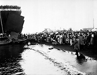 Korean natives prepare to board an LST during the evacuation of Hungnam, while other refugees unload some of their meager belongings from an ox-cart and load them on a fishing boat.  December 19, 1950. (Navy)<br /> NARA FILE #:  080-G-424096<br /> WAR & CONFLICT BOOK #:  1479