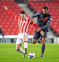 29th December 2020; Bet365 Stadium, Stoke, Staffordshire, England; English Football League Championship Football, Stoke City versus Nottingham Forest; Jordan Thompson of Stoke City is tackled by Lewis Grabban of Nottingham Forest