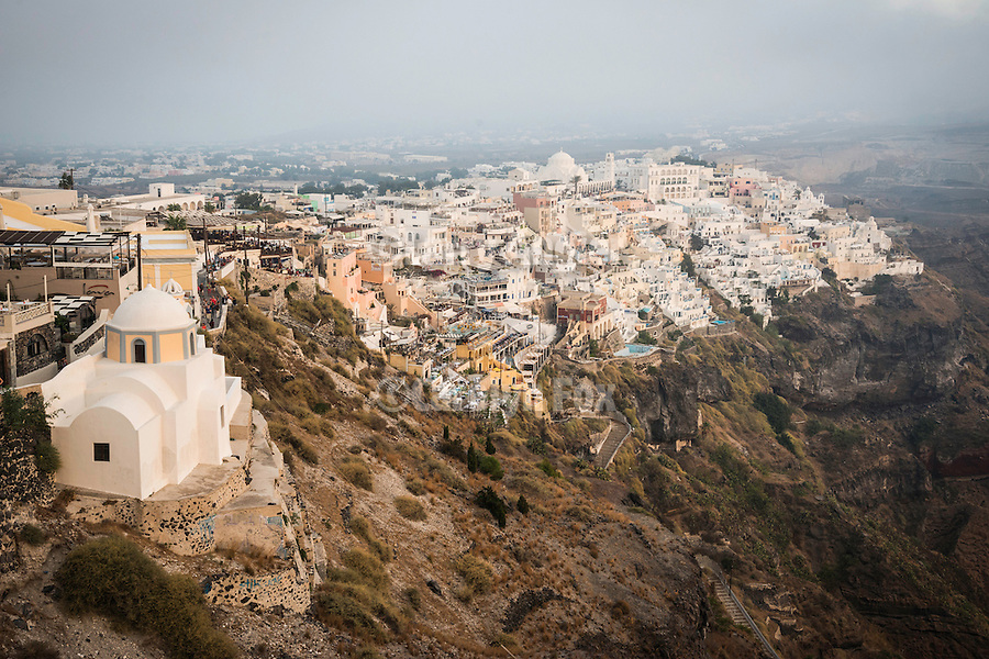 Small Greek Orthodox chapel on a cliff with Fira on the caldera rim in a late summer fog, Santorini, Greece