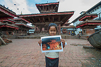Nepal, Kathmandu, earthquake damage at Kathmandu Durbar Square. Girl holding my photo of how the temples looked previously.