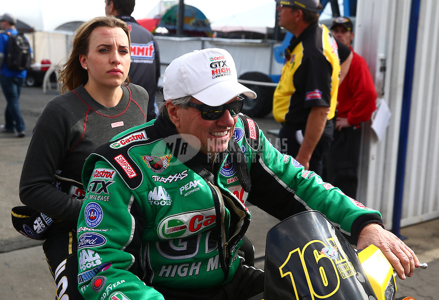 Feb 7, 2014; Pomona, CA, USA; NHRA top fuel dragster driver Brittany Force (back) gets a ride on a scooter with her father NHRA funny car driver John Force during qualifying for the Winternationals at Auto Club Raceway at Pomona. Mandatory Credit: Mark J. Rebilas-